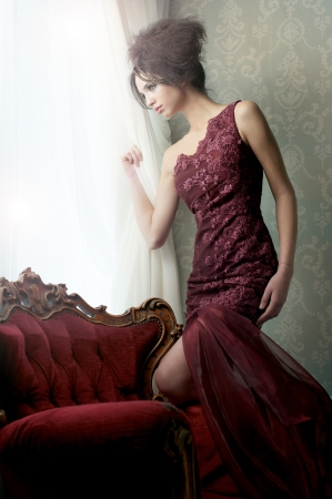Elegant fashion model in red couture wedding dress looking out of the window in expectation. photo