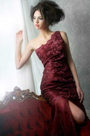 Elegant fashion bride in red wedding dress, looking out of the window. Stock Photo - 17040905