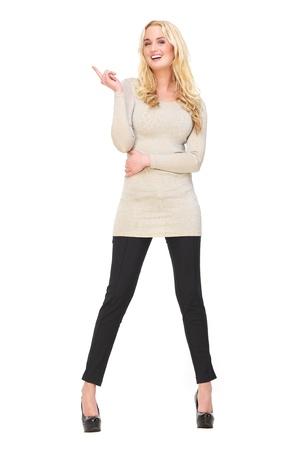 Volledige lengte portret van een mooie jonge vrouw glimlachend en pointin haar vinger omhoog geà ¯ soleerd op witte achtergrond Mogelijkheid voor kopie ruimte Stockfoto