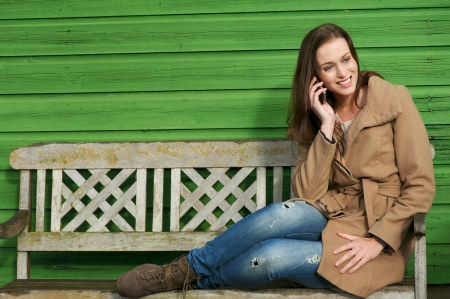sitting on a bench: Cute young female calling on mobile phone outdoors. Happy expression on her face. Sitting on wooden bench with green wall in background. Stock Photo