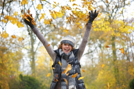 middle age women: Beautiful middle aged woman throwing yellow leaves up in the air