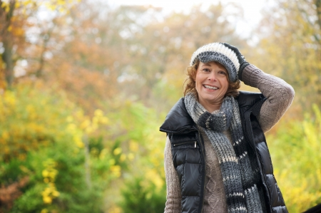 Smiling woman holding winter hat on her head