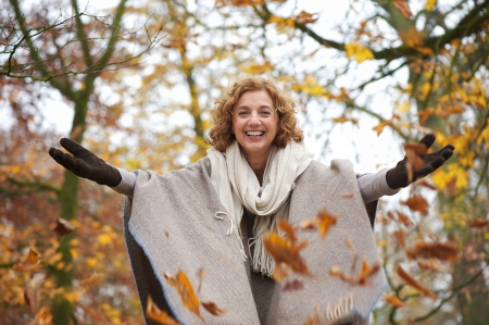 open air: Middle aged woman throwing leaves in autumn with open arms Stock Photo