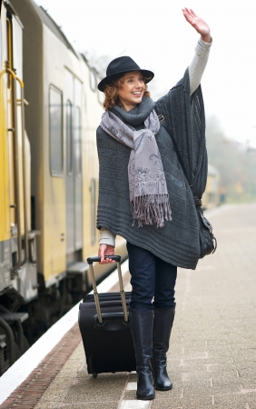 Middle aged woman waving hello on railway station platform photo