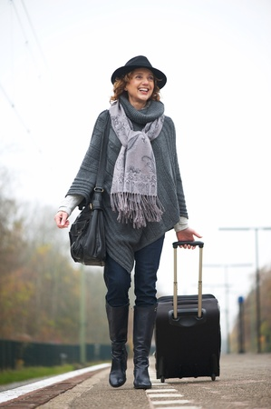 Smiling woman walking on train station platform with travel bag photo