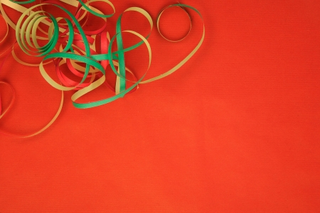 Colored ribbon confetti on a blank red background photo