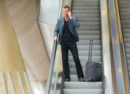 Businessman going down on escalator with phone and bag photo