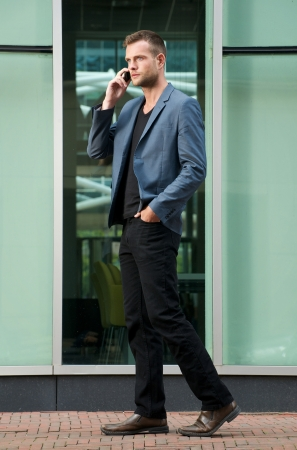 Handsome young man walking and talking on mobile phone in the city photo