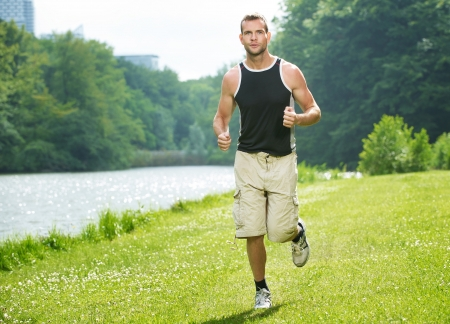 mens: Healthy young man running in the park Stock Photo