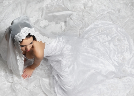 Elegant bride sitting on the floor with long white lace wedding dress