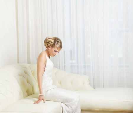 Portrait of a beautiful bride sitting indoors photo