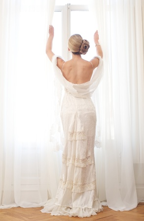 Portrait of a beautiful bride opening a window photo