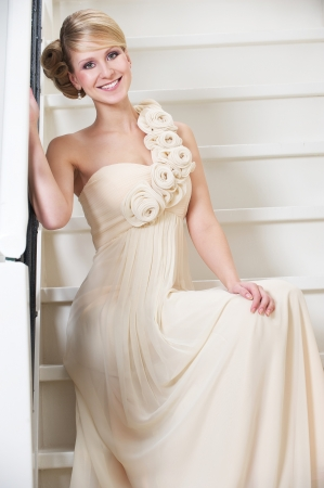 long gown: Portrait of a bride sitting on stairs and smiling Stock Photo