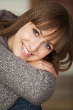 Close up portrait of a young woman smiling indoors