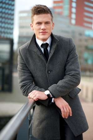 young male model: Portrait of a handsome businessman standing outside