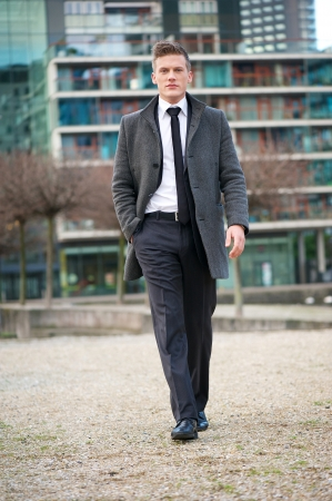 Portrait of a young businessman walking outdoors photo
