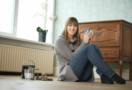 Portrait of a young woman sitting on floor and holding tea cup photo