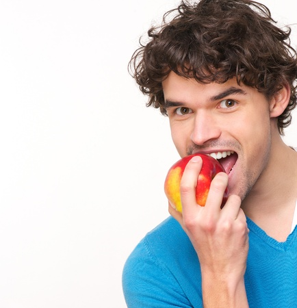 Close up portrait of a young man eating apple photo
