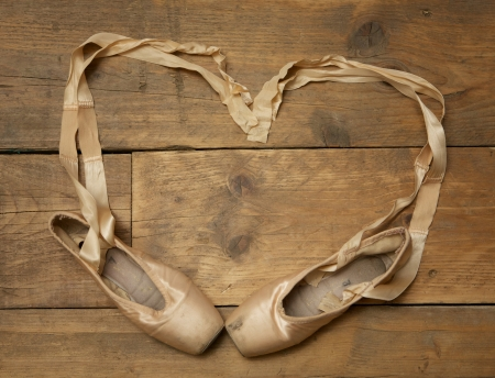 ballet slippers: Pair of ballet shoes on wooden floor with ribbon in heart shape - above view