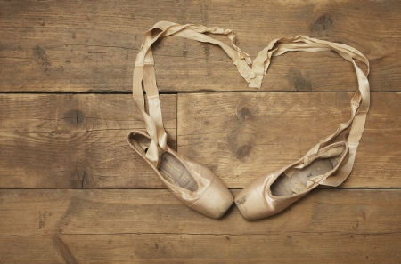 Two ballet shoes on wooden floor with ribbon in heart shape - above view photo