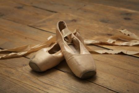 zapatillas de ballet: Un par de zapatillas de ballet utilizadas en el piso de madera Foto de archivo