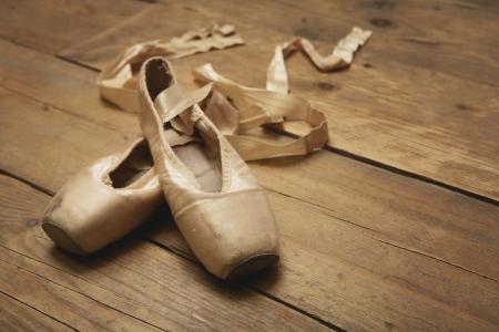 木製の床の上の 2 つのバレエ シューズ