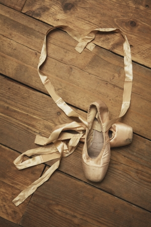 Pair of ballet shoes with ribbon in heart shape - above view photo