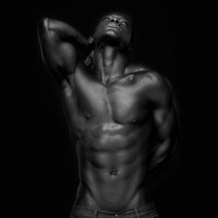 hombre desnudo: Retrato de un atleta afroamericano mirando hacia arriba - en blanco y negro