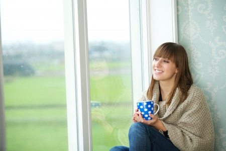 the window: Portrait of a young woman sitting by window with cup of tea