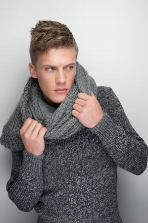 male fashion model: Retrato de una modelo masculino que sostiene la bufanda de invierno