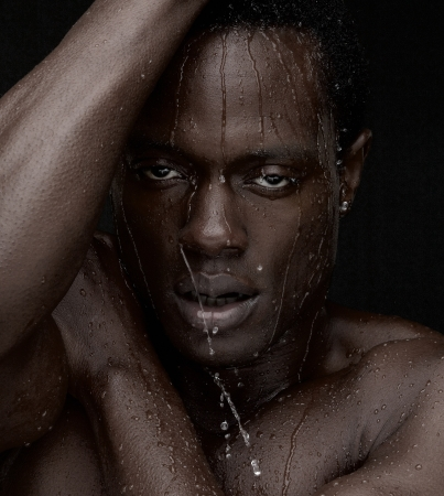 african american nude: Close up portrait of an African American man with water dripping down face