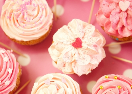 Cupcakes decorated with sprinkles and frosting - close up photo