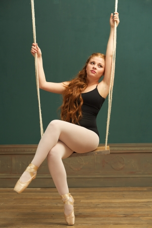 Portrait of a beautiful ballerina sitting on swing photo
