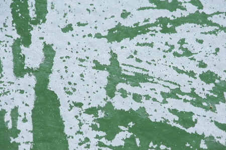 peeled off: Close up of a green wall with white paint scraped off Stock Photo