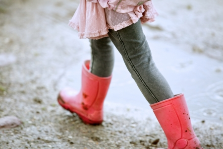 rainy season: Close up little girl walking outdoors with red boots Stock Photo