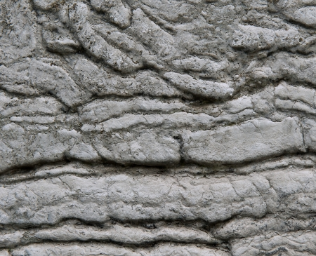warped: Close up aged wall with warped and rippled stone effect