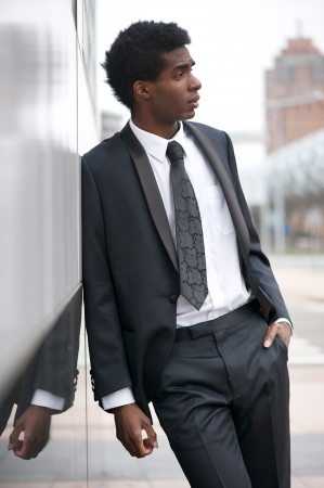 Portrait of a handsome young black man wearing a business suit outdoors in the city photo
