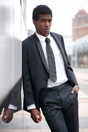 Portrait of a handsome young african american man in a black suit standing in the city photo