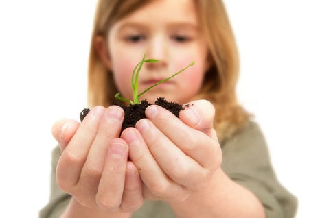 Close up portrait of a little girl holding dirt with plant growing photo