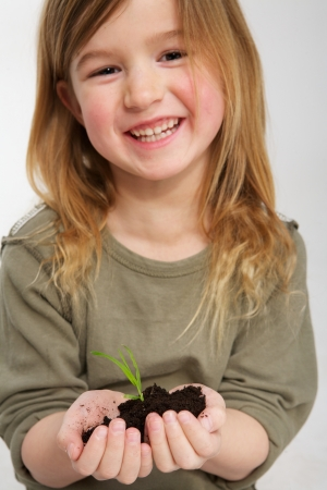Portrait of a smiling girl with plant growing from soil in hands photo