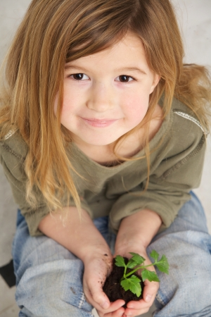 Close up portrait of a child holding plant growing from soil in hands photo