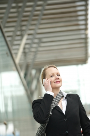 Portrait of an older woman talking on the phone outdoors photo