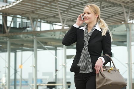 Portrait of a traveling business woman talking on mobile phone outside photo