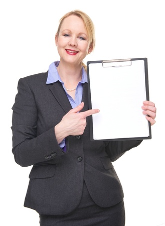 Portrait of a happy businesswoman pointing to empty sign clipboard isolated on white photo