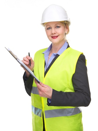 Portrait of a businesswoman in safety vest and hard hat writing on clipboard isolated on white photo