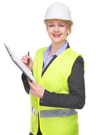 Portrait of a smiling woman in safety vest and hardhat writing on clipboard isolated on white photo