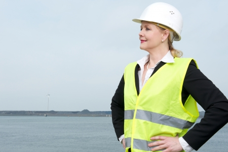 Portrait of a confident businesswoman in hardhat standing outdoors photo