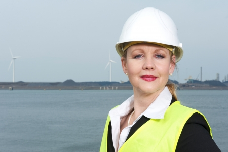 Portrait of a businesswoman in safety vest and hardhat standing outdoors  photo