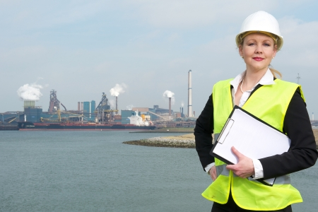 Portrait of a confident businesswoman in hardhat and safety vest holding a clipboard outdoors photo