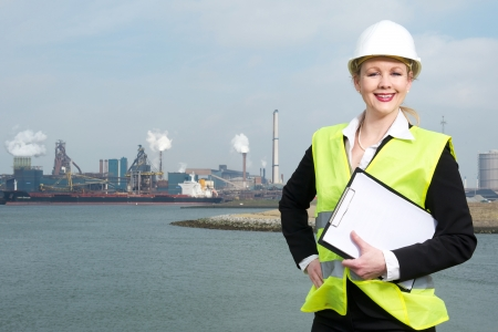 Portrait of a happy businesswoman in hardhat and safety vest standing outdoors with clipboard photo